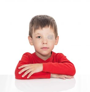 The five-year-old boy sits at a white table, the left eye is stuck with a plaster, sight (vision) stimulation, treatment, load of the right eye, isolated on a white