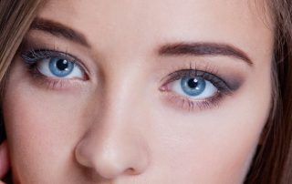Cropped portrait of a woman with a lovely complexion and beautiful big blue eyes wearing subtle eye makeup