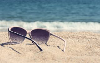 Glasses on the beach sand. Glasses on a background of sea waves